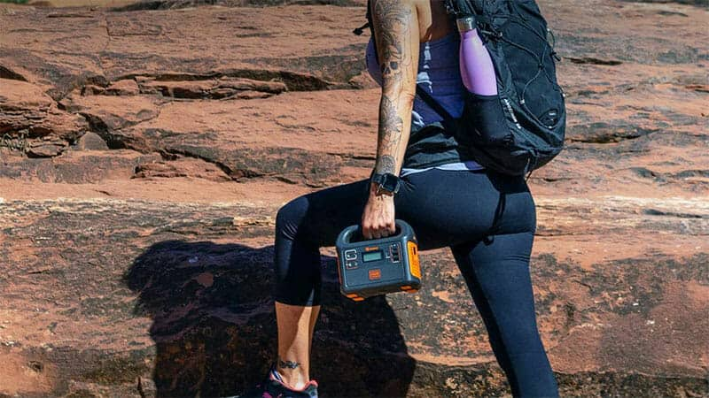 woman carrying a portable battery while on a hike