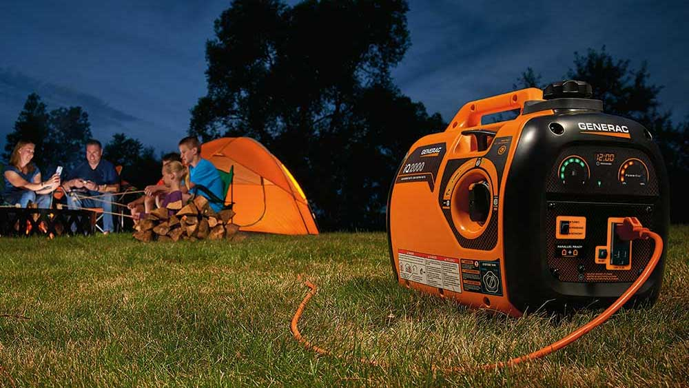 People using a portable generator while camping at dusk