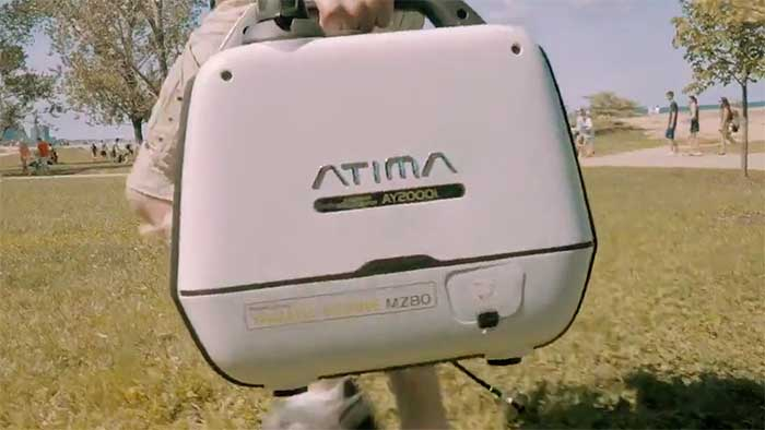 Man carrying a portable generator on a grass field