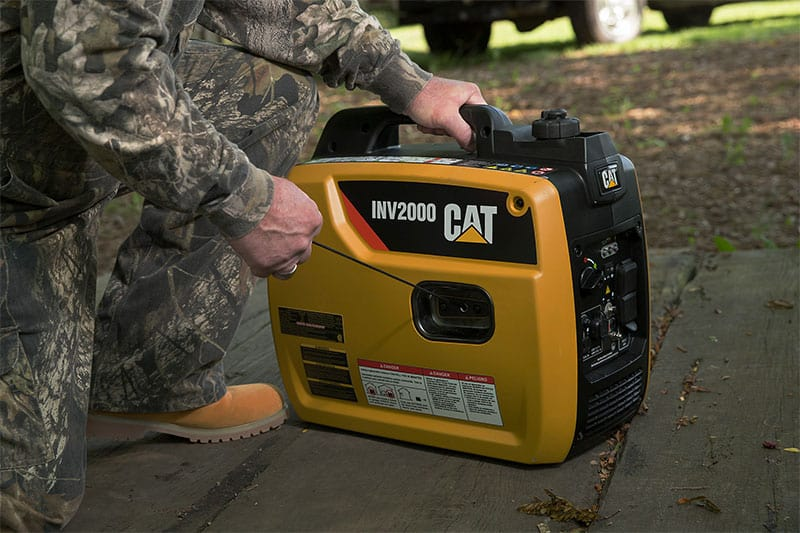 CAT inv2000 generator on the floor with a man handling it