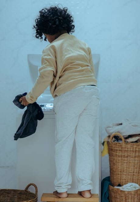 child standing on a chair putting used clothes in a washing machine