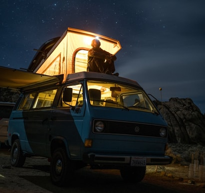 well-lighted RV with a person sitting on top