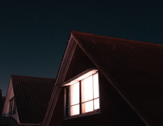 night view of a well-lighted rooftop room from the outside