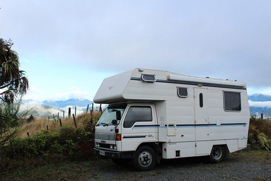RV parked at a side of a rocky road