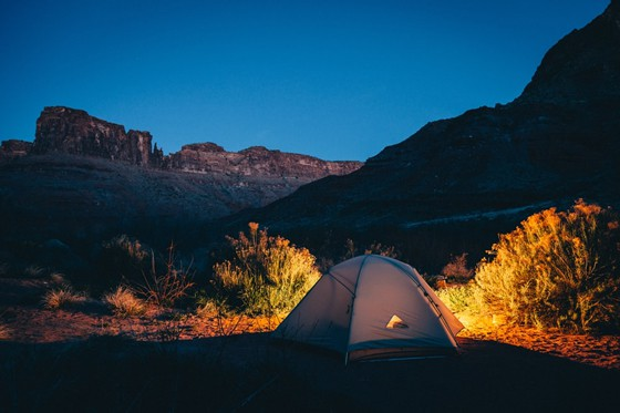 well-lighted tent set up in between mountains