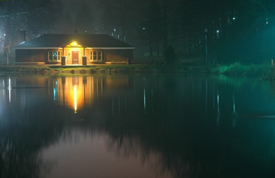 well-lighted house beside a lake