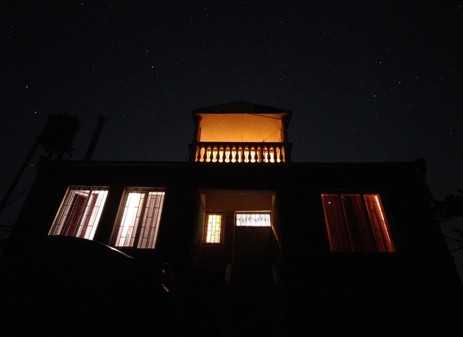 front view of a house with a well-lighted rooftop balcony