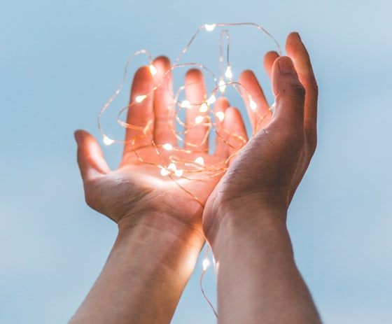 two open hands carrying series lights
