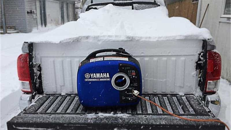 Blue generator on a car trunk in the snow