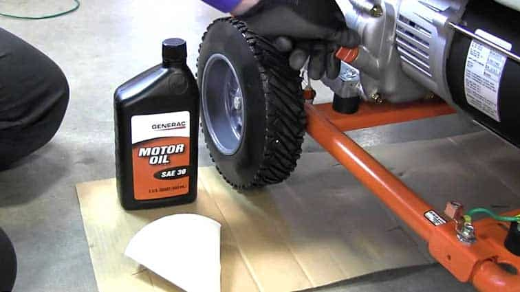 Bottle of motor Oil next to a portable generator