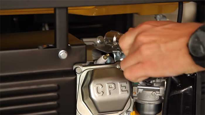 hand removing the spark plug on a generator