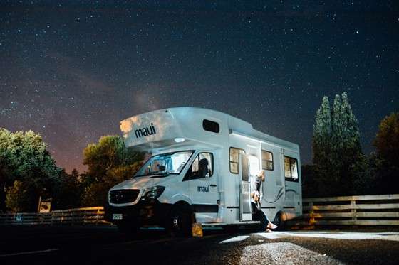 well-lighted RV with a lady sitting at the door
